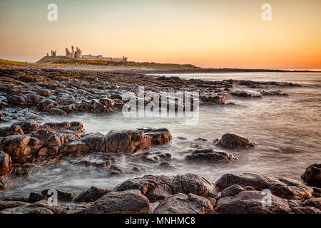 Sunrise at Dunstanburgh Castle on the Northumberland coast, North East England. - Stock Photo