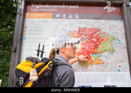 Ranger of Triglav National Park pointing at map of area whilst guiding tourist around Krn mountain in southwestern Julian Alps in northwestern Slovenia - Stock Photo