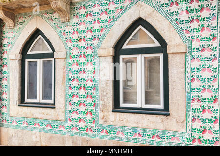 7 March 2018: Lisbon, Portugal - Arched windows and ceramic tiles decorating an old building in the Alfama district. - Stock Photo