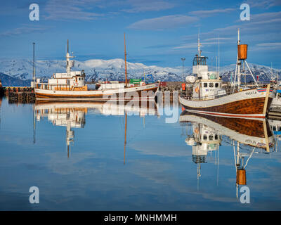 13 April 2018: Husavik, Iceland. The harbour at Husavik in Northern Iceland, with whale-watching vessels reflected in the calm water.