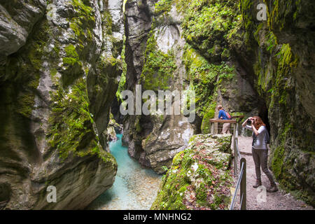 Tourists enjoying majestic natural scenery of the Tolmin gorge in Triglav National Park, Slovenia - Stock Photo