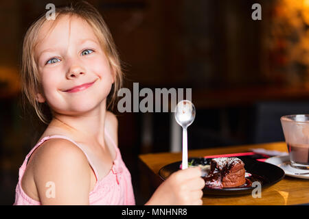 Casual portrait of adorable little girl making funny face enjoying meal at restaurant - Stock Photo