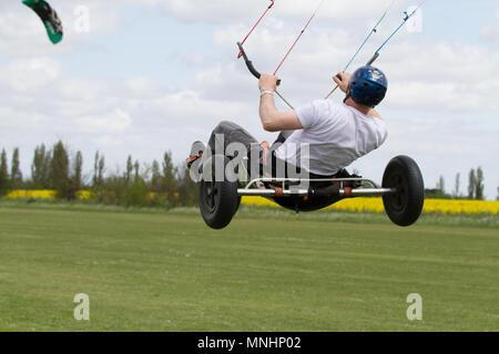 Extreme sport kite landboarding in Essex, UK. Airborne in a land buggy.. - Stock Photo