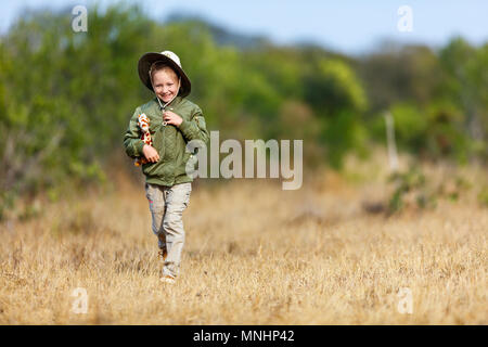 Adorable little girl in South Africa safari running in a bush with giraffe toy - Stock Photo