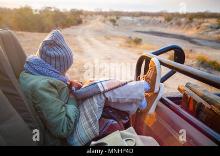 Adorable little girl wearing warm clothes outdoors on beautiful winter morning safari game drive - Stock Photo
