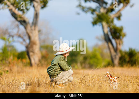 Adorable little girl in South Africa safari with giraffe toy - Stock Photo