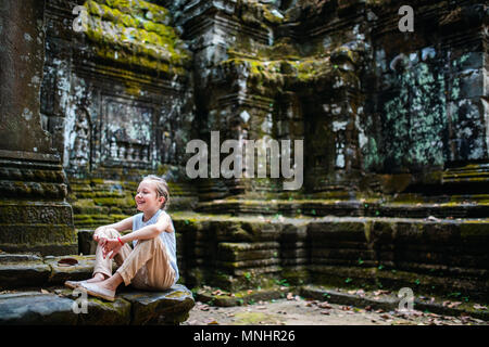 Little girl in ancient Angkor Wat temple in Siem Reap,  Cambodia - Stock Photo
