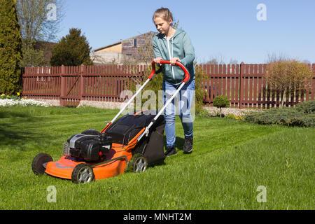 teenage girl mowing grass - Stock Photo