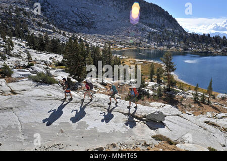 Backpackers hike above Grouse Lake on their way to Grouse Lake Pass on a two-week trek of the Sierra High Route in Kings Canyon National Park in California September 2012. The 200-mile route roughly parallels the popular John Muir Trail through the Sierra Nevada Range of California from Kings Canyon National Park to Yosemite National Park. - Stock Photo