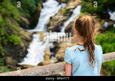 Young girl enjoying views over Ravana Ella waterfalls in Sri Lanka from a viewpoint - Stock Photo
