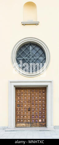 Old wooden door and round window with metal grid - Stock Photo