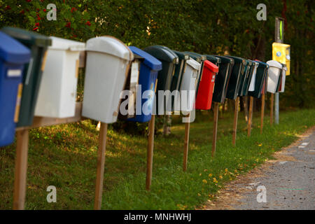 Mailboxes in a row along a small Swedish road for efficient mail delivery. - Stock Photo