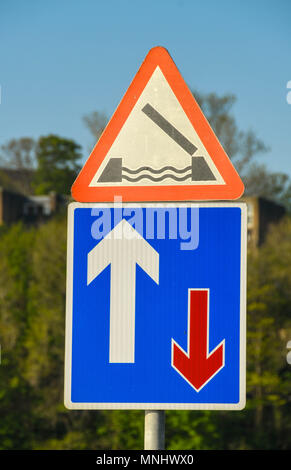 Road sign on the Cardiff Bay barrage warning of a lifting road bridge and priority over oncoming traffic - Stock Photo