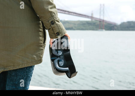 The girl is holding virtual reality glasses. Bridge April 25 in Lisbon in Portugal in the background - Stock Photo