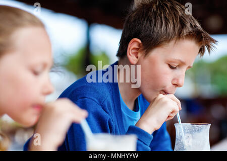 Kids brother and sister drinking milkshakes in outdoor cafe - Stock Photo