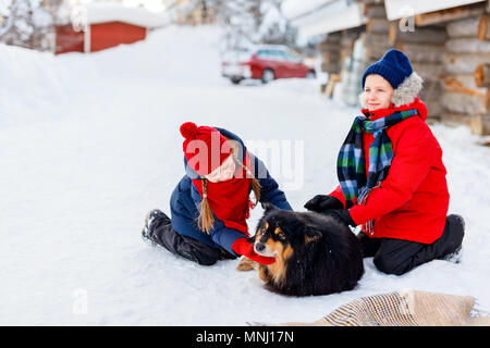 Kids brother and sister having a cuddle with dog in Lapland Finland - Stock Photo