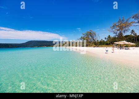 Kids having fun at tropical beach during  summer vacation playing together at shallow water - Stock Photo