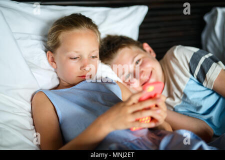 Kids brother and sister playing on a portable game device or smartphone - Stock Photo