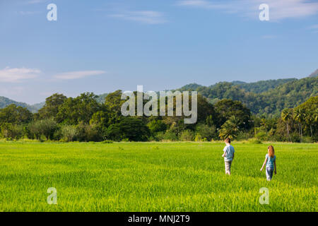 Kids brother and sister enjoying peaceful walk in rice field with breathtaking views over mountains in Sri Lanka - Stock Photo