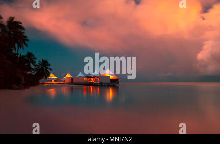 Romantic beach landscape, little restaurant on the bank of tropical island at the evening, summer vacation on a luxury resort, Maldives - Stock Photo