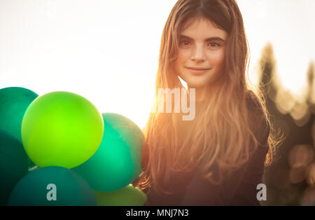 Portrait of a cute girl with air balloons outdoors in mild evening sun light, celebrating birthday, holidays and fun concept - Stock Photo