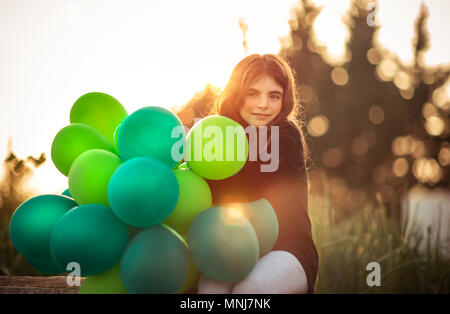 Portrait of a cute little girl sitting in the park with pile of green air balloons outdoors in mild evening sun light, celebrating birthday, preparati - Stock Photo