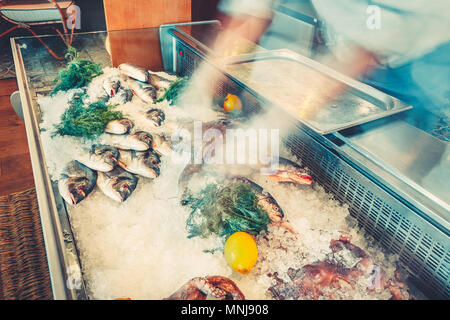 The freshly caught fish and the octopuses are lying in the ice with the lemons and dill in the refrigerated counter of the restaurant. Fresh seafood f - Stock Photo