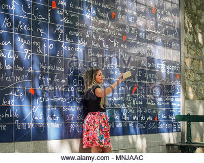 PARIS, FRANCE-MAY 6, 2016: Young woman makes selfie next to wall of love (aka I Love You Wall) in the Jehan Rictus garden square in Montmartre - Stock Photo