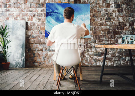 Professional painter sits on chair in front of easel with canvas, hold paintbrush in hand and drawing oil painting. Artist working process in studio.  - Stock Photo