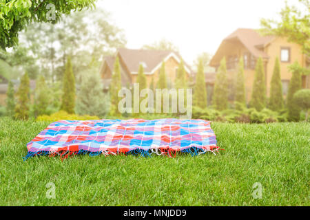 Bright checkered mat on green grass lawn under trees in garden. Blurred wooden houses on background. Empty space for product display. Picnic concept - Stock Photo