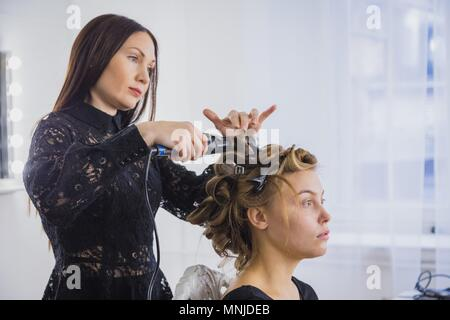 Professional hairdresser doing hairstyle for young pretty woman - making curls - Stock Photo