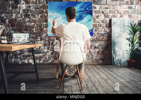 Artist in art studio sits on chair in front of canvas on easel and drawing. Painter work in workshop. Working process. Hobby concept - Stock Photo