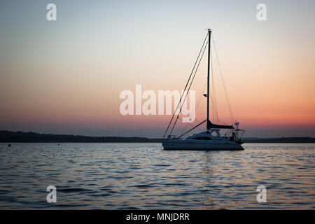 Small boat moored off the shore at Poole Harbour - Stock Photo