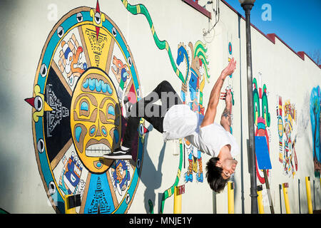 Young parkour athlete doing backflip off wall covered in street art, Denver, Colorado, USA - Stock Photo
