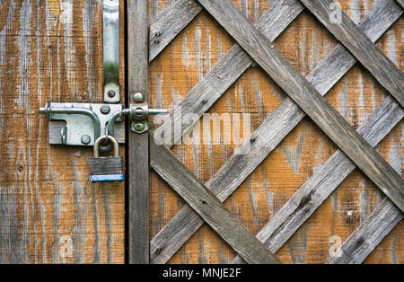The old wooden door with diagonal square discolored hammered thin laths is closed on metal latch and padlock for secure storage of household items - Stock Photo