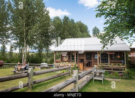 Hikers enjoying drink outside bar in log cabin, Polebridge, Glacier National Park, Montana, USA - Stock Photo