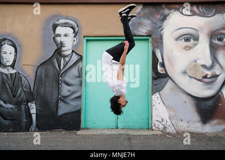 Young fit parkour athlete doing backflip in front of street art, Santa Fe Arts District, Denver, Colorado, USA - Stock Photo