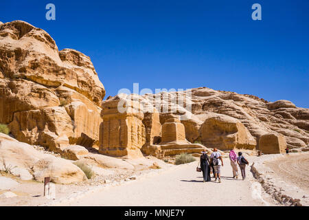 Tourists walking on footpath in Petra with tombs and temples carved in sandstone, Wadi Musa, Maan Governorate, Jordan - Stock Photo
