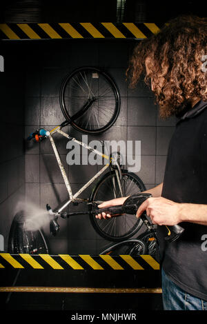 Services professional washing of a bicycle in the workshop. Close-up of hand Young Caucasian stylish man doing bicycle cleaning using automatic electric water pump. Sprays scatter from the pressure - Stock Photo