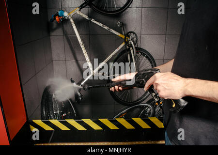 Services professional washing of bicycle in the workshop. Close-up of hand Young Caucasian stylish man doing bicycle cleaning using an automatic electric water pump. Sprays scatter from the pressure - Stock Photo