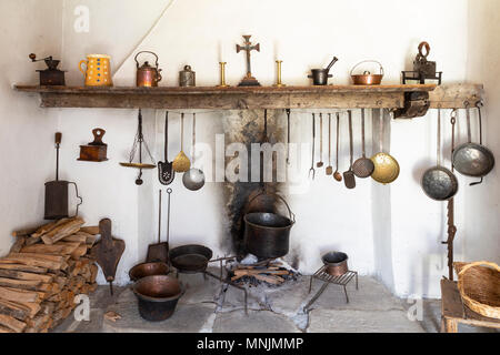 Front view of a retro style rustic kitchen with open fireplace, cooking tools, pans, and various other kitchen equipment - Stock Photo