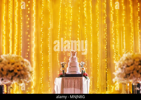 Beautiful four layers wedding on the table on stage decoration with LED light in yellow golden theme with part of biuquet flower blurry in foreground - Stock Photo