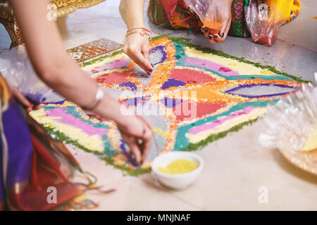 Women helps coloring tradition colorful rice art or sand art (Rangoli) on the floor with paper pattern using dry rice and dry flour with colored from  - Stock Photo