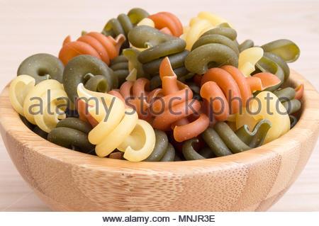 Italian pasta in three spiral colors - Stock Photo
