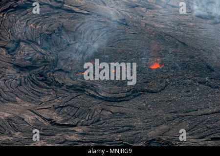 Lava and poison gases bubble out from a fissure caused by the eruption of the Kilauea volcano at Leilani Estates May 17, 2018 in Pahoa, Hawaii. The recent eruption continues destroying homes, forcing evacuations and spewing lava and poison gas on the Big Island of Hawaii. - Stock Photo