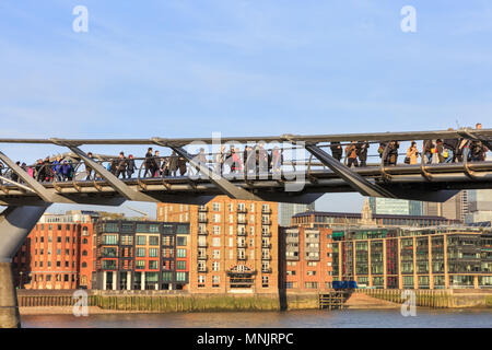 People walking across the Millennium Bridge above the River Thames on a beautiful sunny day, London, England, UK - Stock Photo