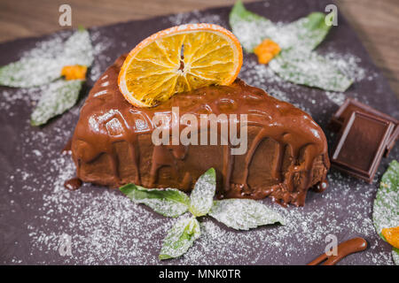Chocolate dessert with orange chips on a wooden background - Stock Photo