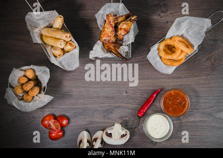 Snack for beer in the form of nuggets cheese rings and fried chicken legs - Stock Photo
