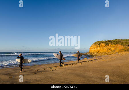 Three surfers at Bells Beach, Torquay, Surf Coast Shire, Great Ocean Road, Victoria, Australia - Stock Photo