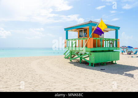 Miami South Beach, lifeguard house in a colorful Art Deco style at sunny summer day with the Caribbean sea in background, world famous travel location - Stock Photo